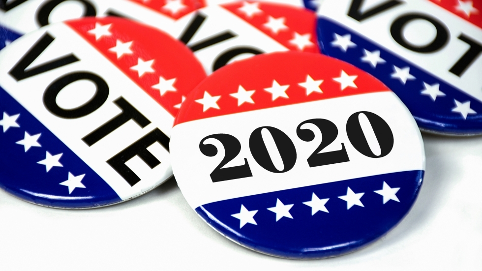 "A collection of red, white and blue buttons that read ""Vote"" and ""2020"""