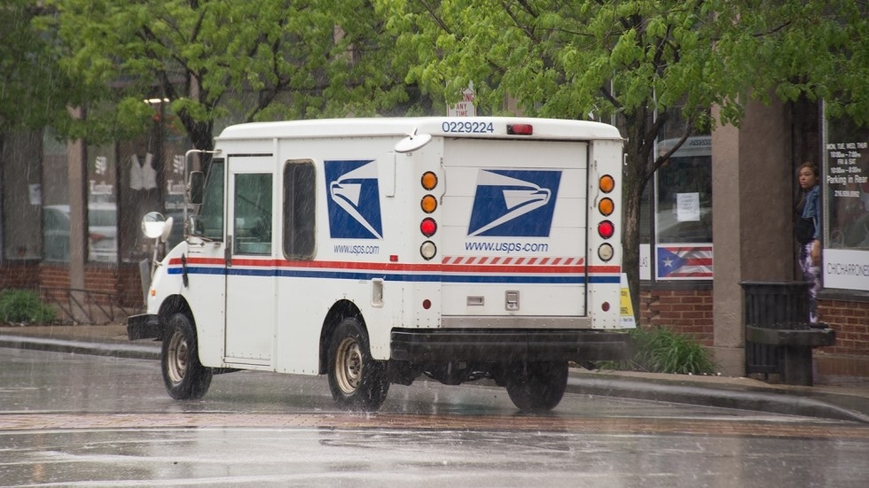 A US postal truck driving in the rain