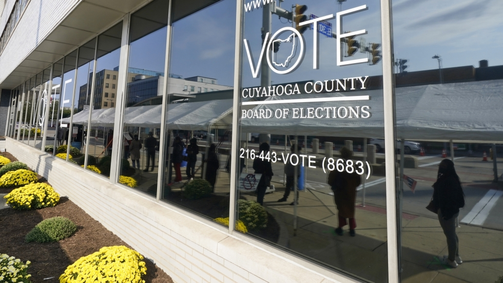 Voters are reflected in a window as they wait in line to participate in early voting at the Cuyahoga County Board of Elections, Tuesday, Oct. 6, 2020, in Cleveland.