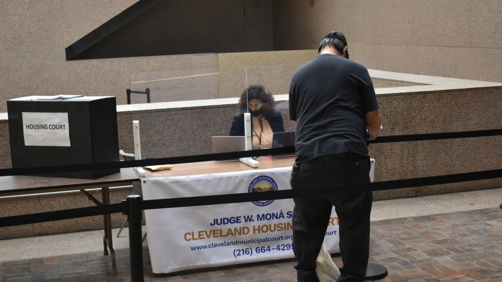 a woman at a table with a housing court sign sits behind a plastic partition while a man with his back to the camera fills out paperwork in the lobby of the Justice Center in Downtown Cleveland
