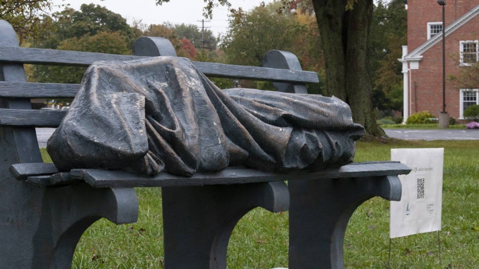 A statue of Jesus as a homeless man lies on a bench outside St. Barnabas church in Bay Village, Ohio.