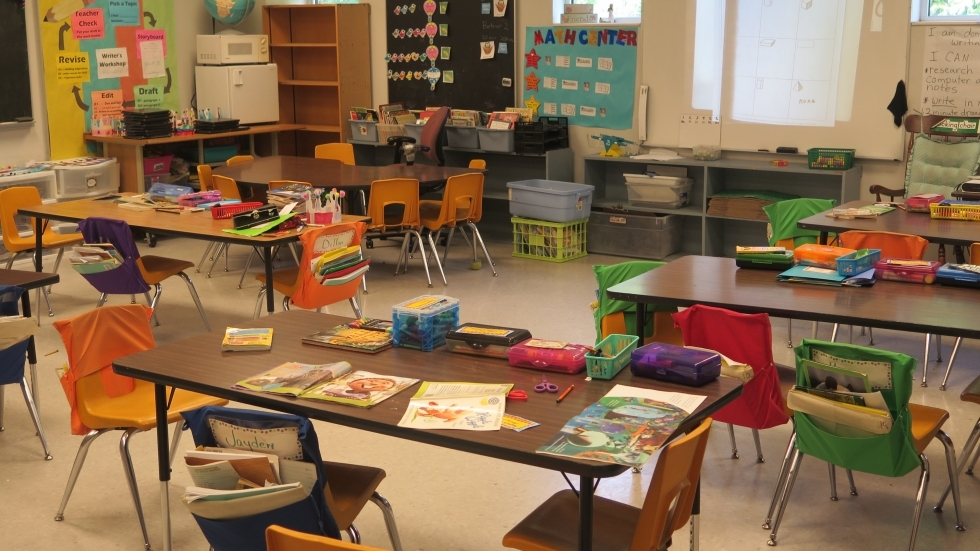 An empty classroom with supplies on the desks