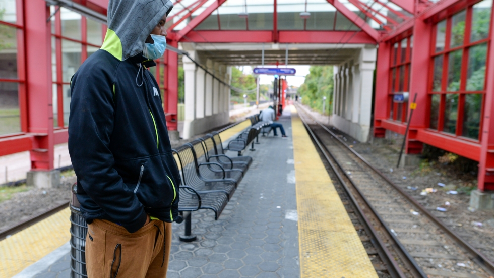 A masked rider waits for a train at a Greater Cleveland Regional Transit Authority (RTA) rail stop.