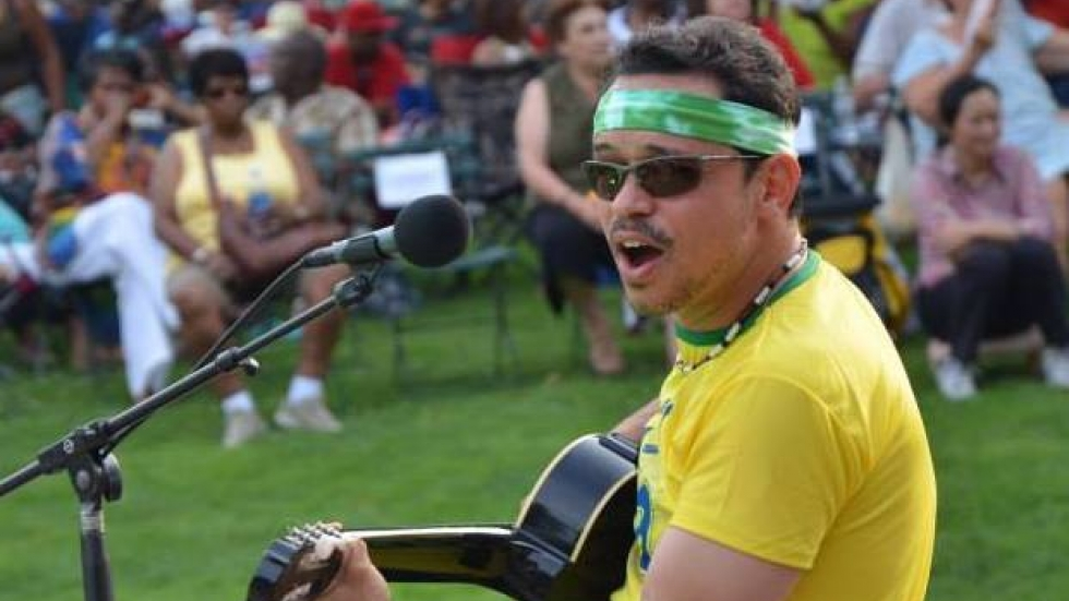 The Brazilian-born Cleveland musician plays his guitar at an outdoors concert.