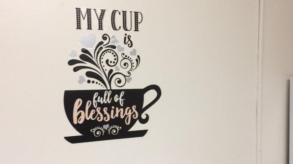 "A stencil on Quiana Baker's wall reads ""my cup is full of blessings."""