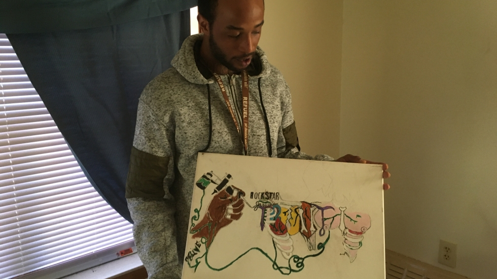 Marquel Hawkins holds a piece of his artwork.