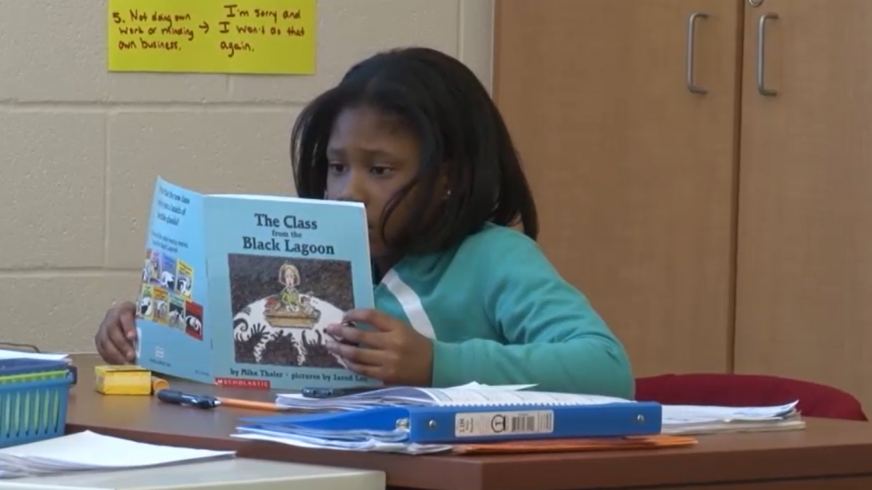 Student at Akron Schools reads a book at her desk