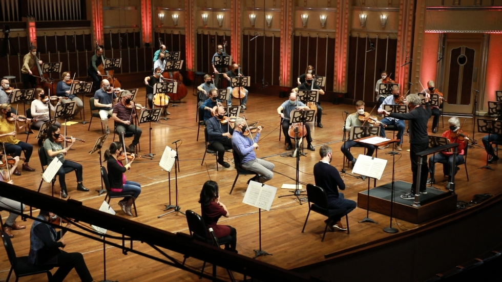 The masked and socially distanced strings of the Cleveland Orchestra rehearse for an on-line performance.