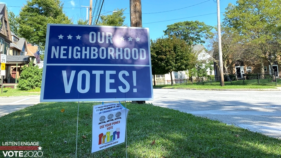 A sign encouraging voting is posted on a tree lawn in Cleveland's Detroit-Shoreway neighborhood.