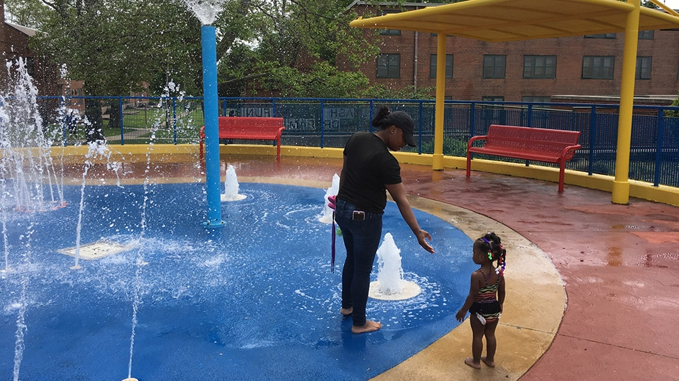 A mother guides her daughter at a splash park at Woodhill Homes.