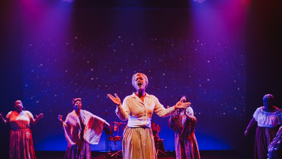 Costumed women sing from the Karamu stage about the African American experience