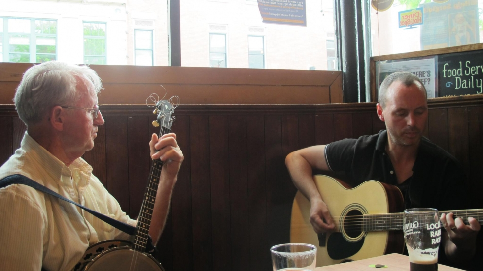 Terence McQuinn with his banjo and son Eoin playing guitar, make music in an Irish bar over a couple of pints of beer. [Eoin McQuinn]
