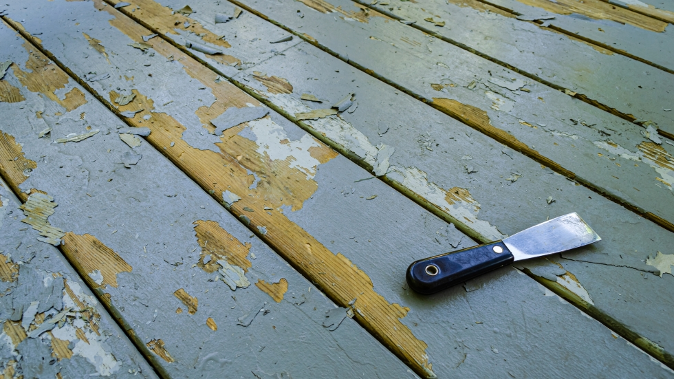 A putty knife laying on gray wooden boards next to paint chips.