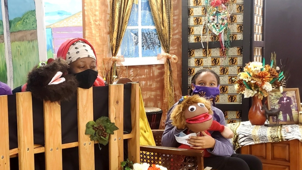 """Two young, masked puppeteers on the set of """"Mr. Stevie's Neighborhood"""" at the Foluke Cultural Arts Center."""