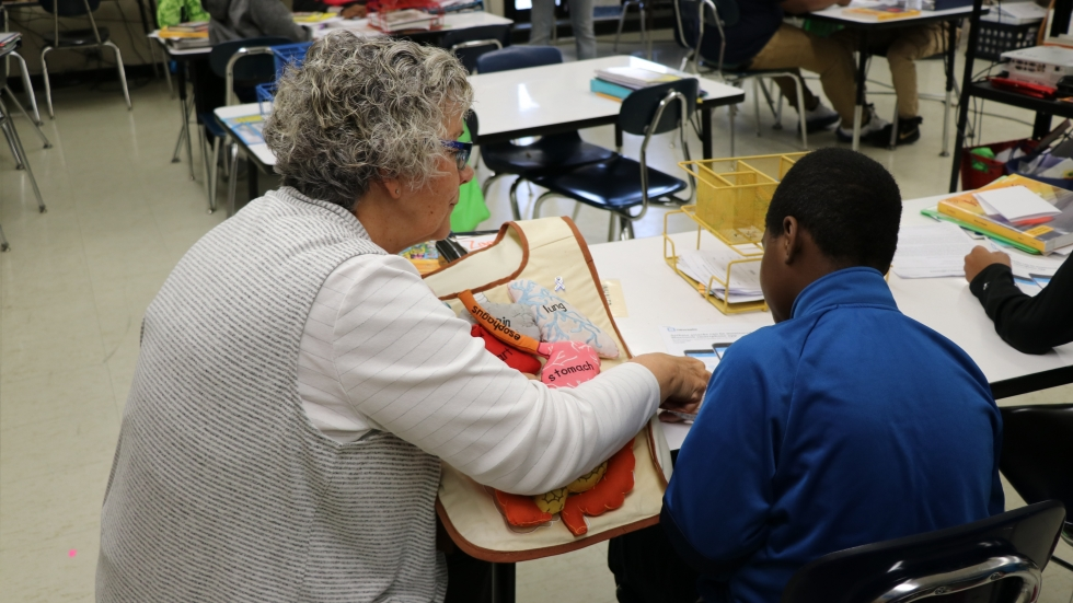 Barb Israel shows a fifth grade student at Marion-Sterling Elementary in Cleveland an article about healthy breathing.