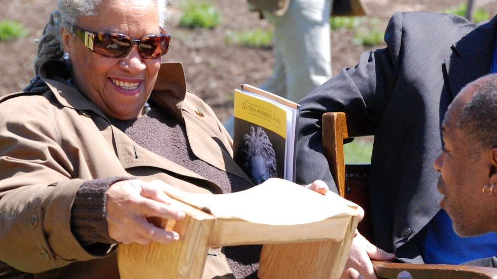 Novelist Toni Morrison smiles as she examines a West African-inspired foot stool given to her by Johnny Coleman in 2009