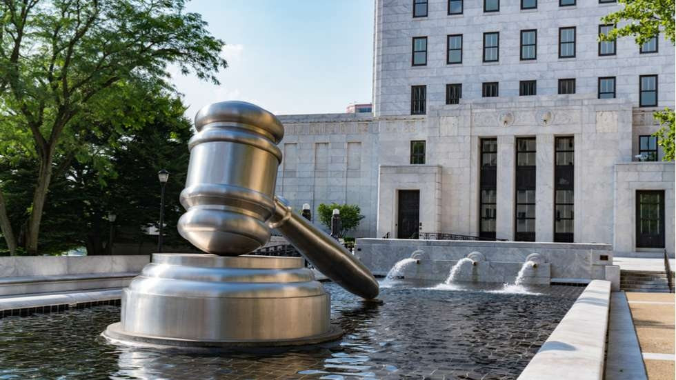 A statue of a gavel in a fountain outside the Ohio Supreme Court.