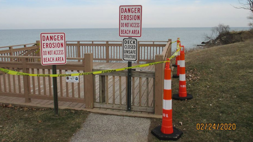 Signs, caution tape and cones warn people to stay off the wooden overlook deck in Mentor-on-the-Lake.
