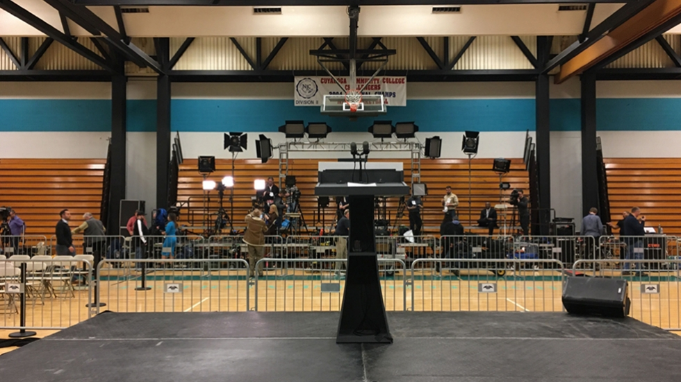 empty stage and bleachers with journalists and television cameras in the background