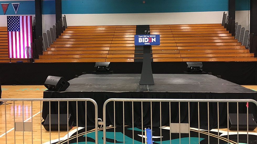 empty stage and bleachers with a Biden 2020 sign on a podium at center stage