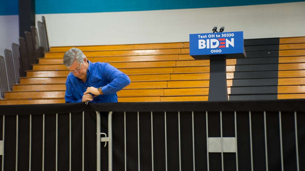 man dismantling stage with Biden 2020 sign on a podium and empty bleachers behind him