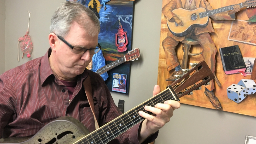 Kevin Richards plays a battered, 1930s guitar under an image of blues legend Robert Johnson.