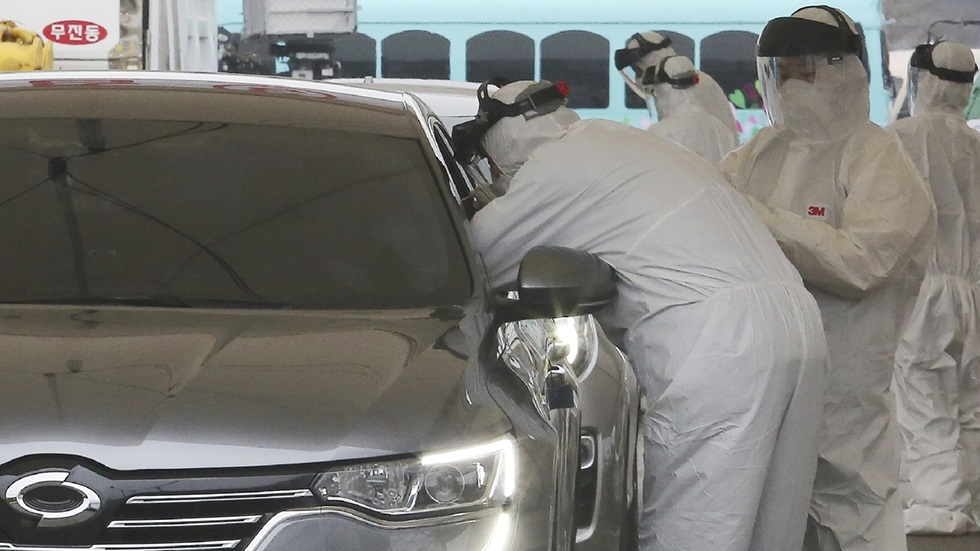 """Medical staff wearing protective suits take samples from a driver with symptoms of the coronavirus at a """"drive-through"""" virus test facility in Goyang, South Korea, Sunday, March 1, 2020. [Ahn Young-joon / AP]"""
