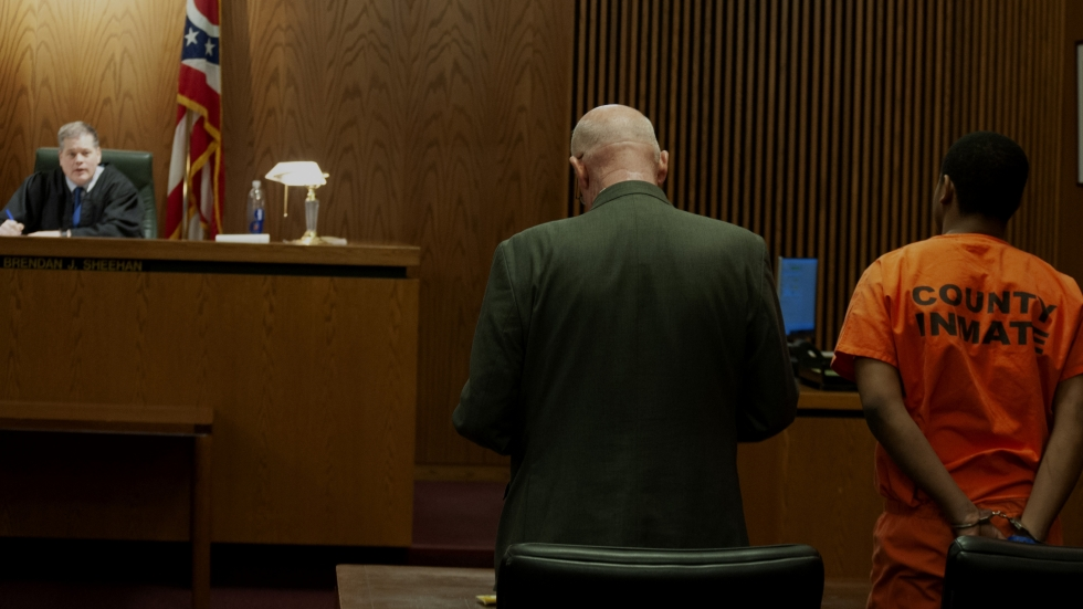 A judge sits at his bench Saturday before a defendant in an orange jumpsuit in a Cuyahoga County court hearing Saturday.