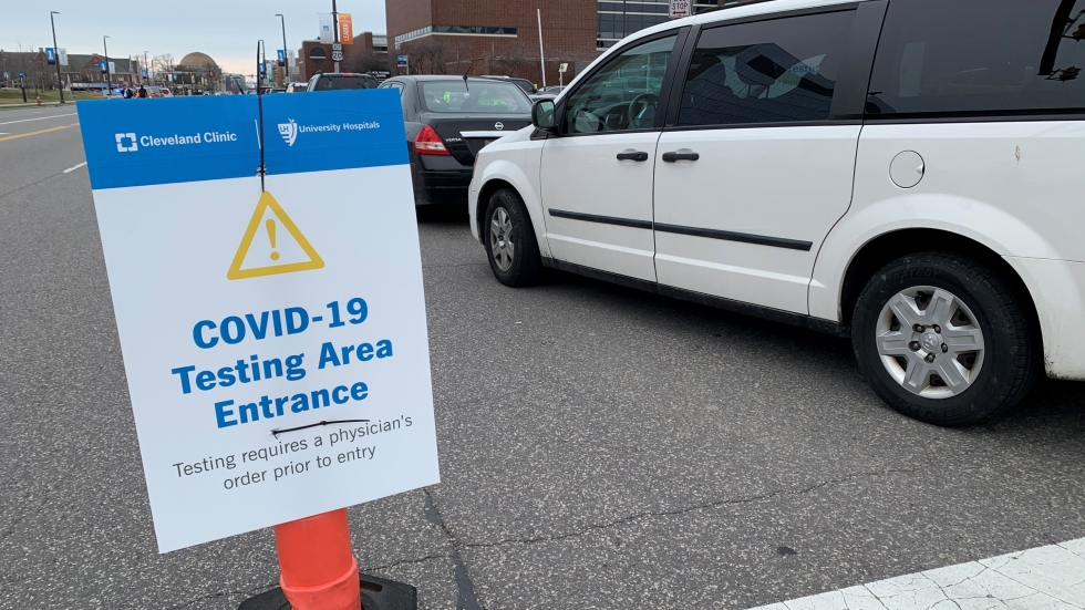 Cars line up for drive-thru COVID-10 testing near University Circle. A sign warns a doctor's order is required.