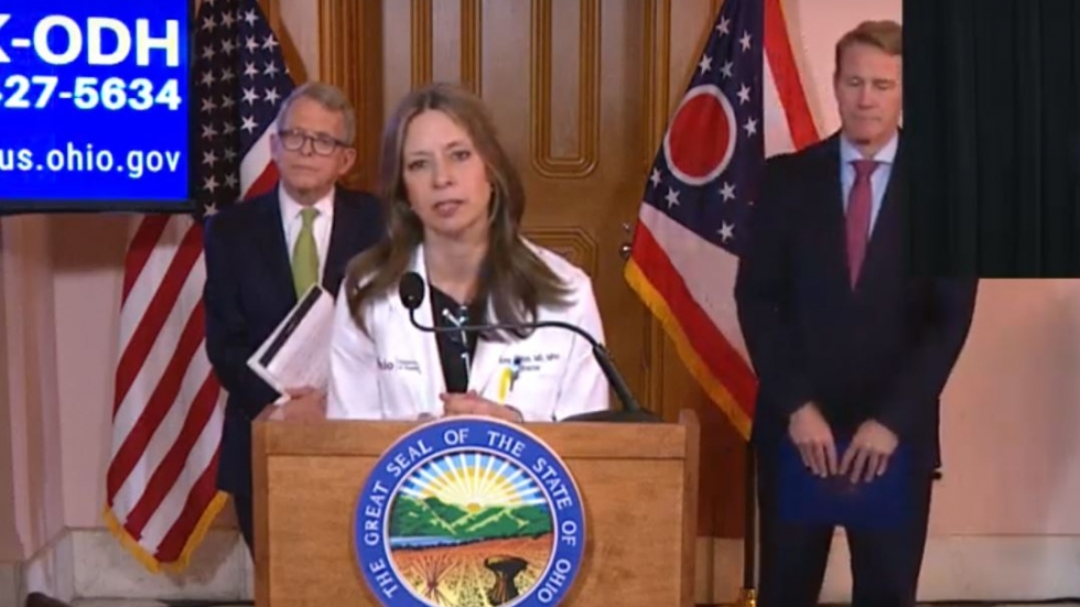 Dr. Amy Acton at a podium in the Ohio Statehouse