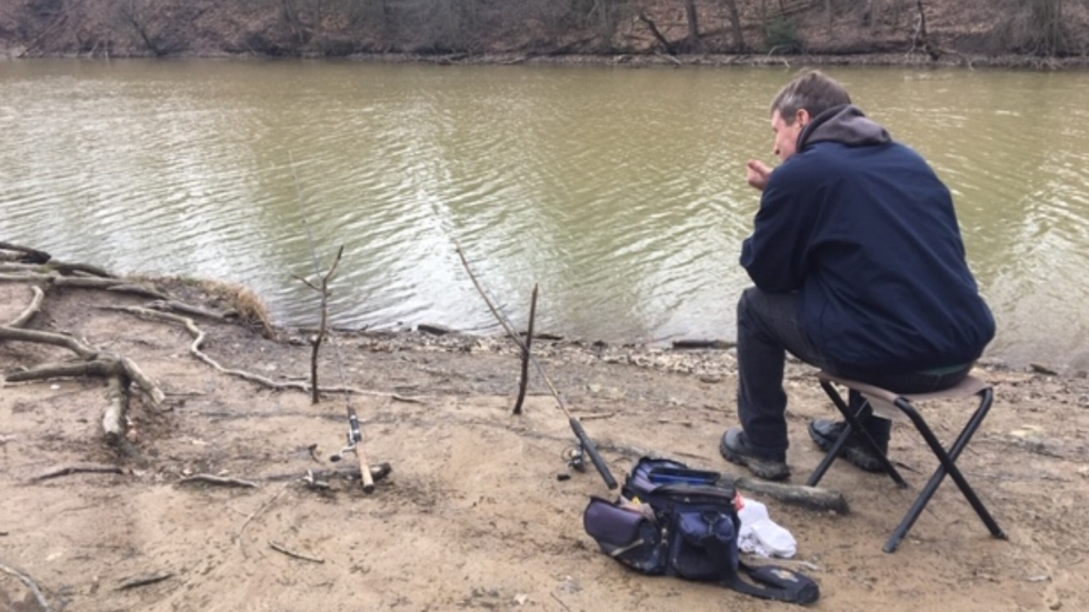 A man fishes from shore at the Cleveland Metropark's Wallace Lake