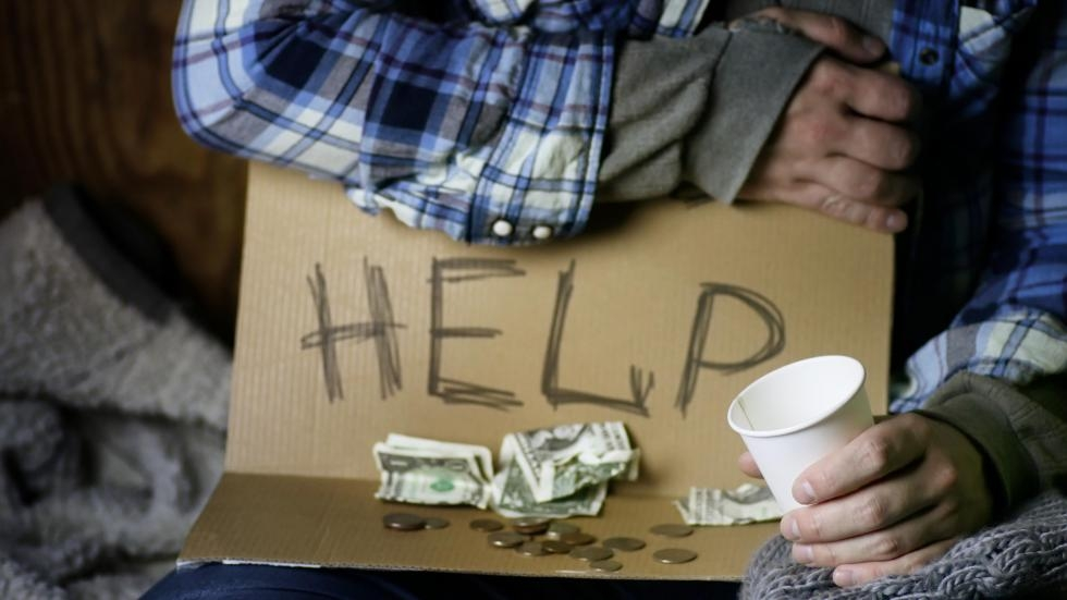 """A person holding a sign that reads """"HELP"""" and holding out a cup. The sign has a few dollars and change on it."""