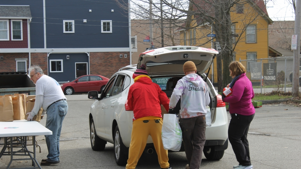 Volunteers load food and supplies into a car at the May Dugan Center's drive-thru pantry in Ohio City on Wednesday, March 25.