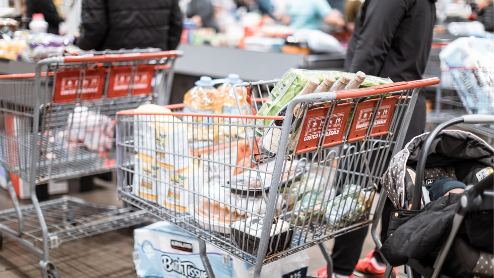 A full shopping cart in a line of people checking out at a grocery store.