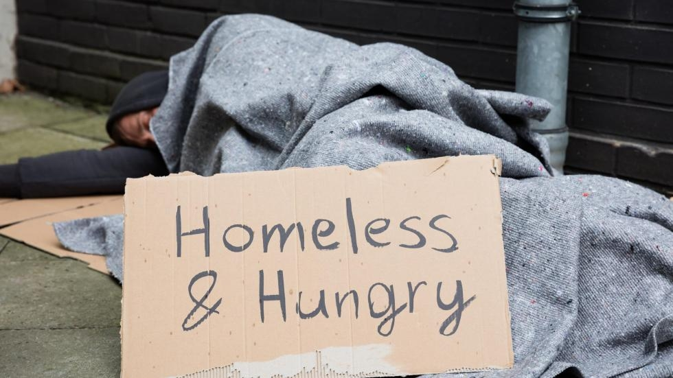 "A man lying on the sidewalk with a sign that reads ""Homeless and hungry"""