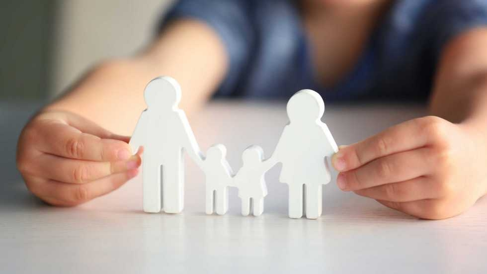 Two hands holding a paper cutout of a family