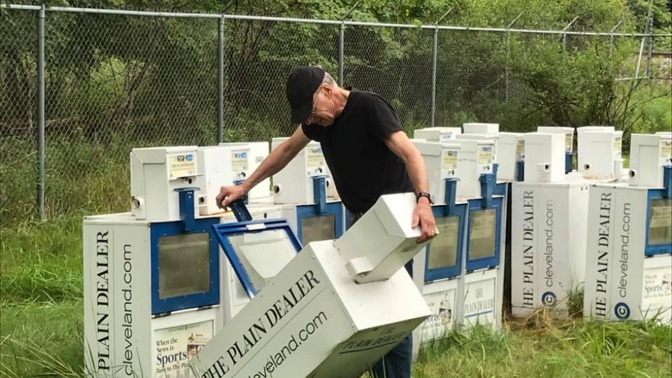 A man looks at a group of empty Plain Dealer newspaper boxes.