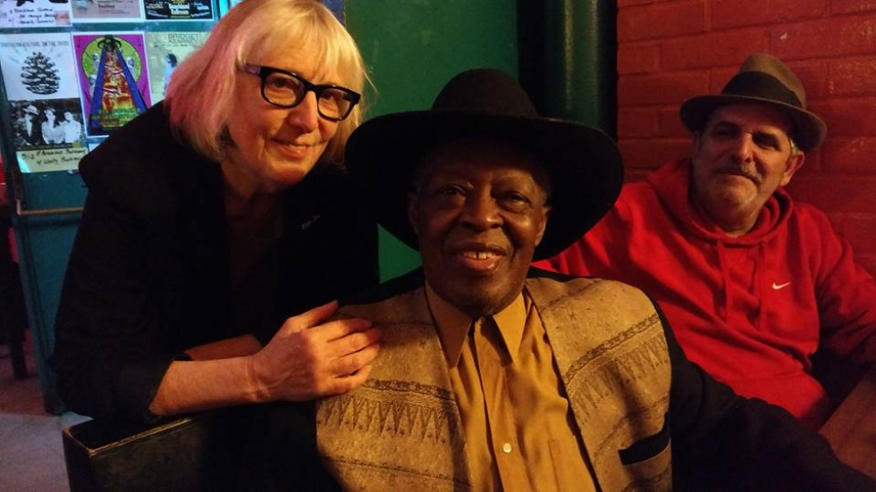 """A bespectacled Cindy Barber gives a hug to Cleveland blues legend """"Crazy Marvin"""" Braxton in a big black fedora."""