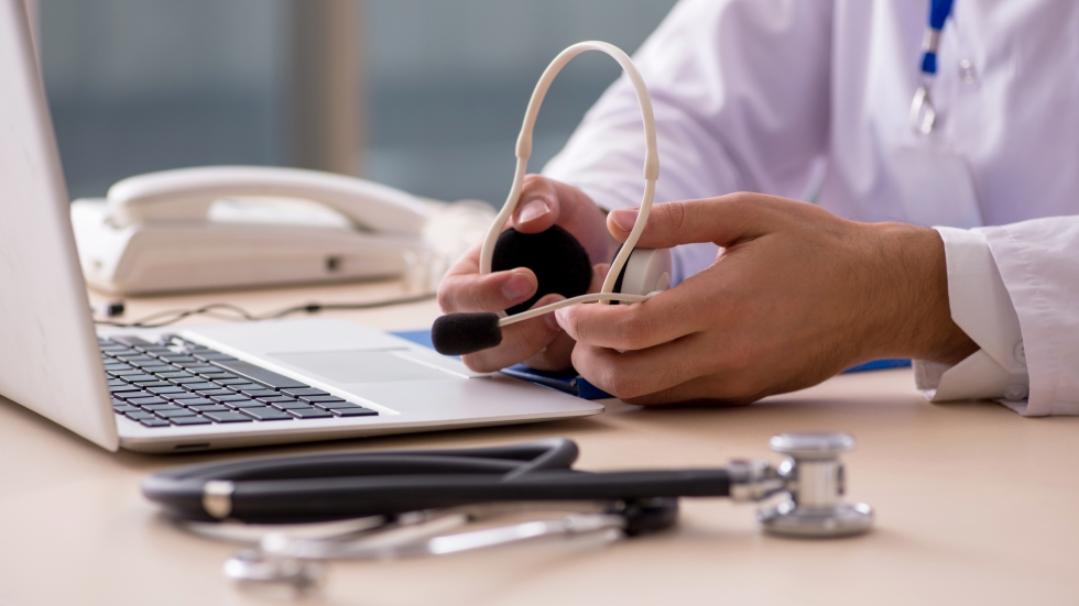 A medical professional holds a set of headphones while facing a laptop screen.