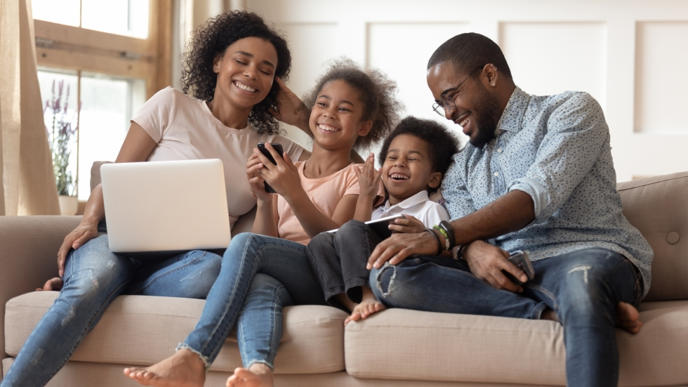 Family of four looking at a computer and cellular phone.