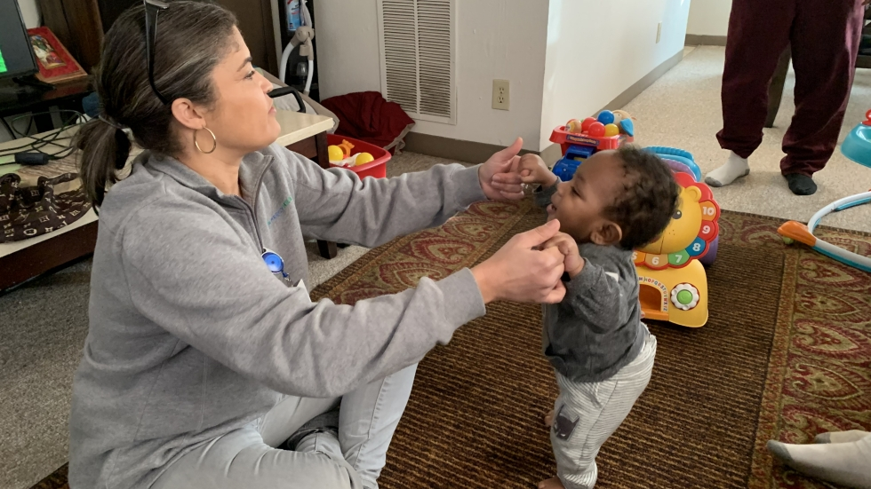 Community health worker Jill Sands plays with a client's infant during a home visit in Elyria in January. In Cuyahoga County, home visit programs have switched to remote care due to the COVID-19 pandemic.