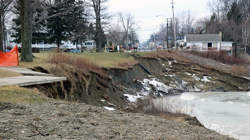 A sidewalk in Township Park hanging over the eroded shoreline, surrounded by barriers.