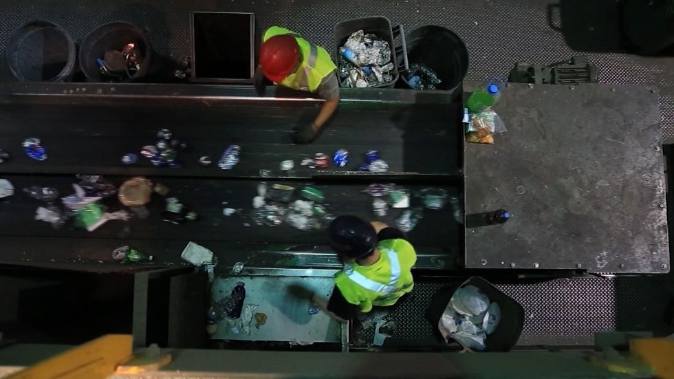 a conveyer belt in a recycling facility, from above, with two workers beside it.