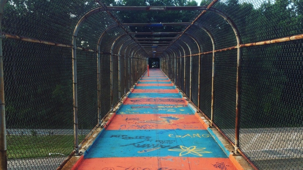 A colorful, graffiti-splashed footbridge spans a highway to connect two Cleveland neighborhoods