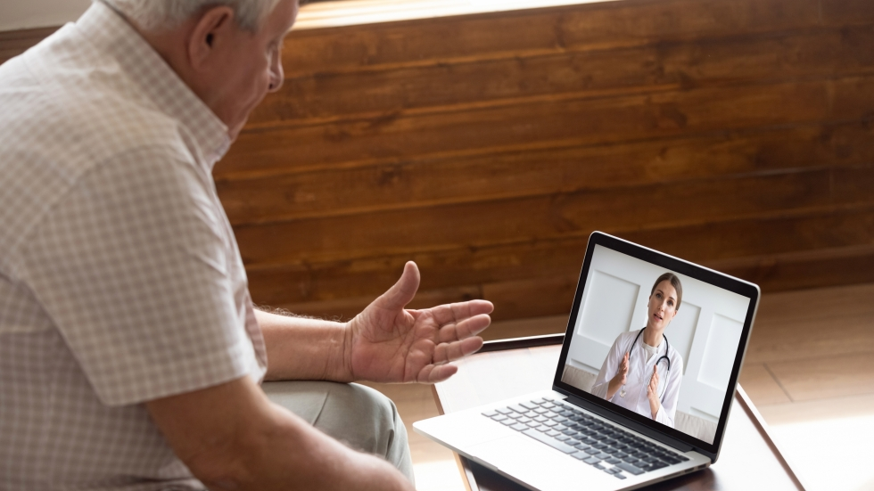 Man talks to doctor on a computer screen during a virtual telemedicine visit.