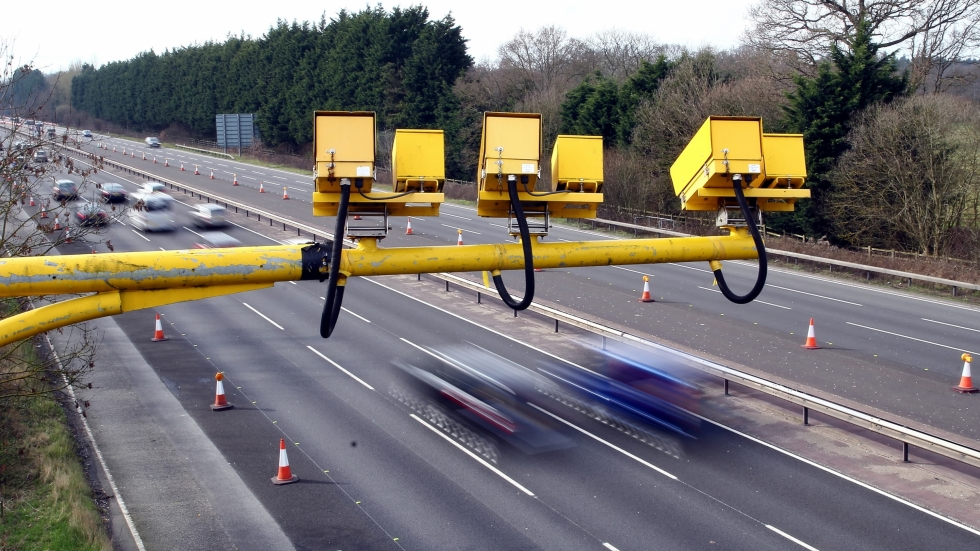 Traffic cameras over a highway as cars go by.