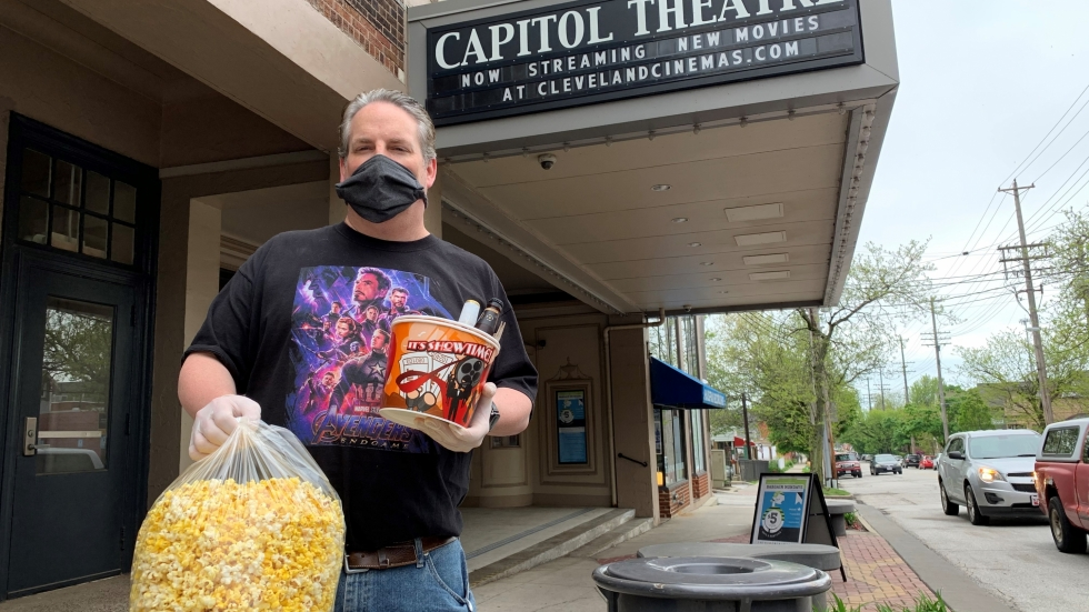 "A masked Jeff Belter delivers a big bag of popcorn and drinks to a ""Curbside Concessions"" customer"