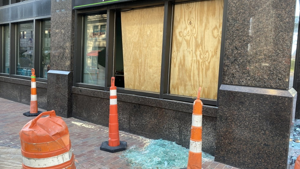 Boards of plywood cover shattered windows of the pHuel Cafe in Cleveland's Playhouse Square on June 1, 2020.