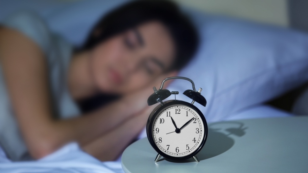 woman sleeping in a bed next to an alarm clock