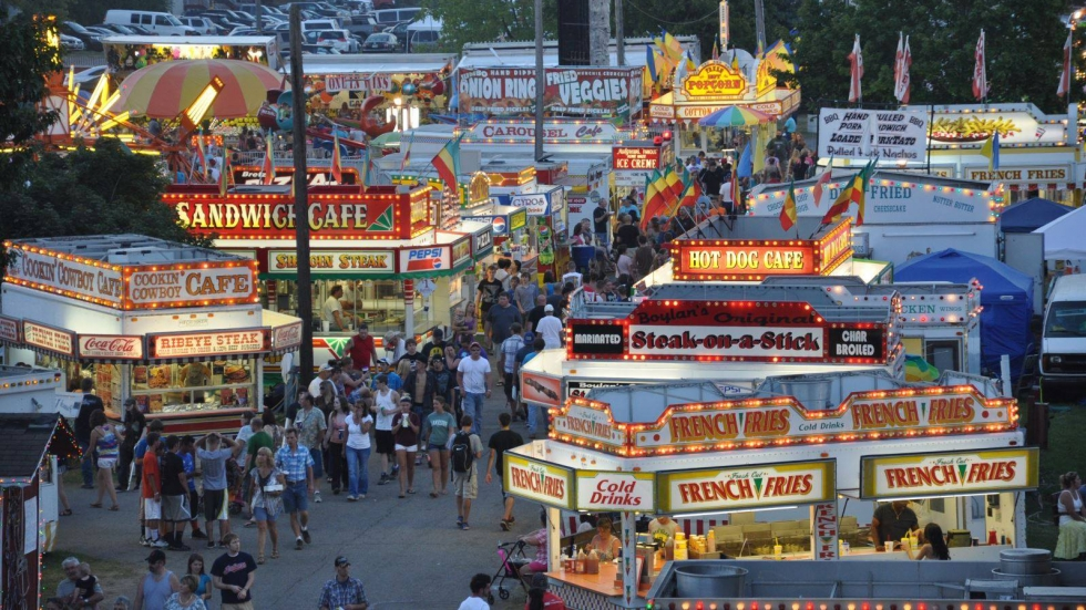 Fair attendees walking down a lit up thoroughfare with food stalls and rides.